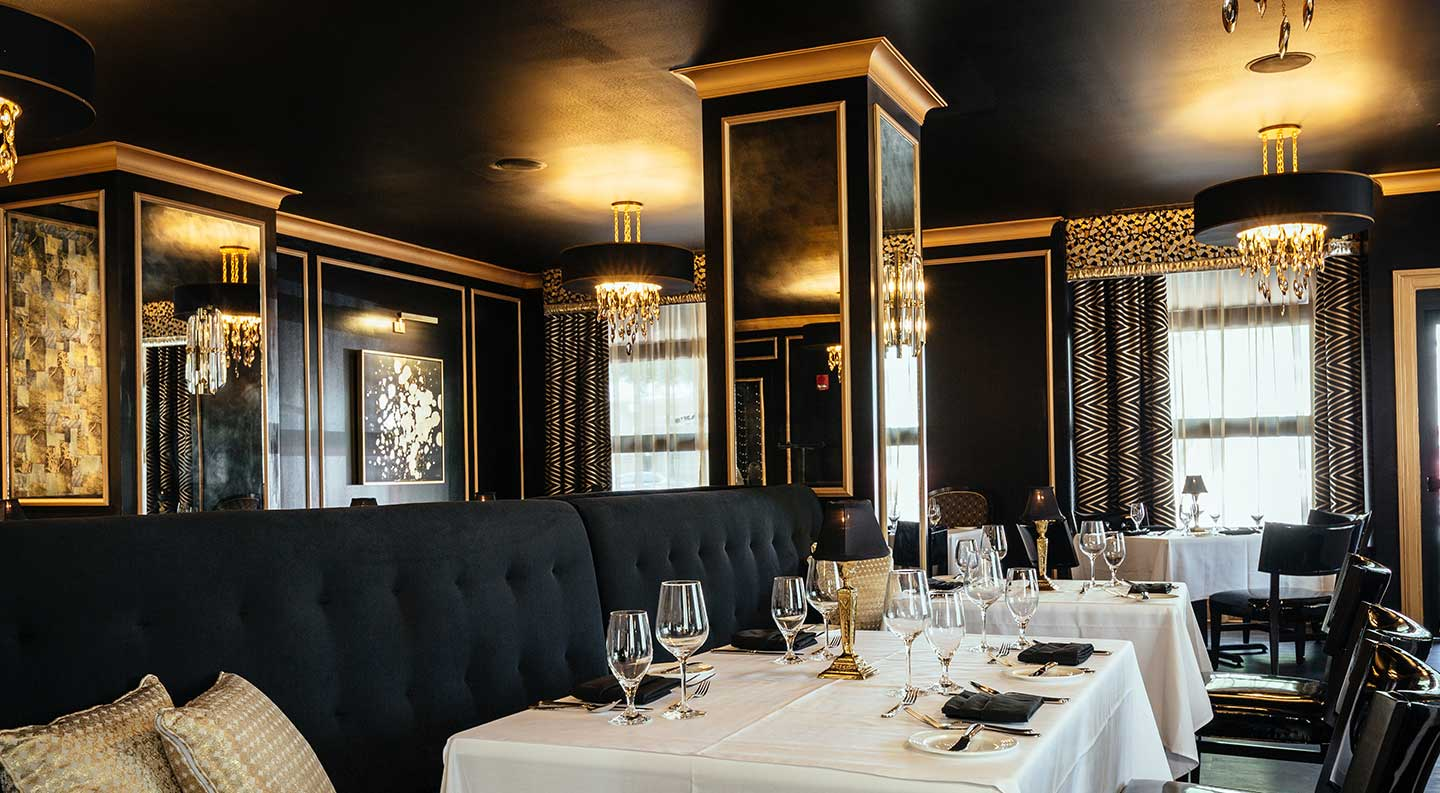 The Bridgeman's Chophouse dining room with white table cloths, rich dark walls with gold accents, and ornate hanging lights