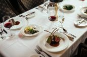 A table set with a white table cloth and containing glasses of red wine and luxurious dishes like rack of lamb and filet mignon