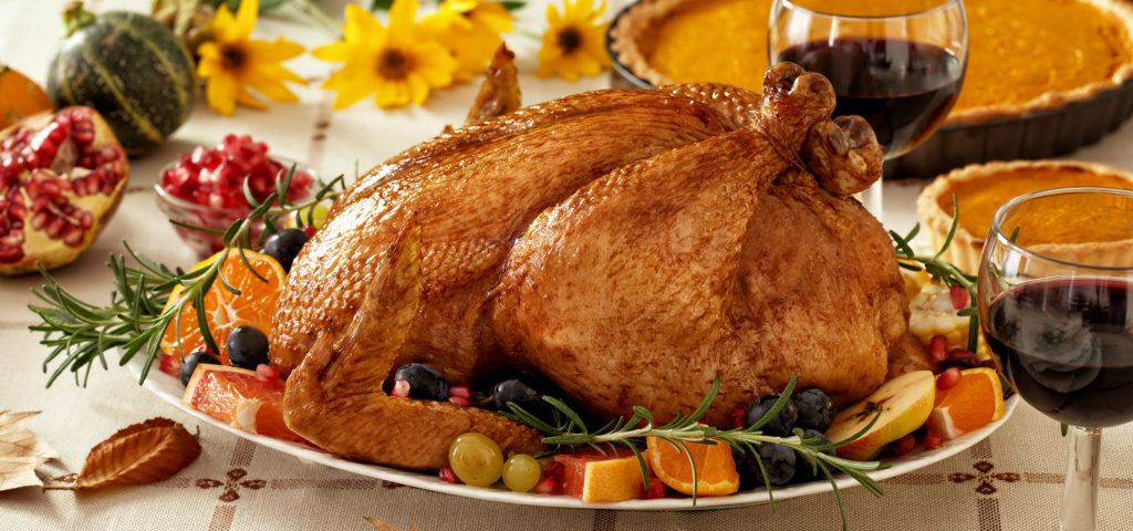 A roasted Thanksgiving turkey on a table with pumpkin pies and glasses of red wine